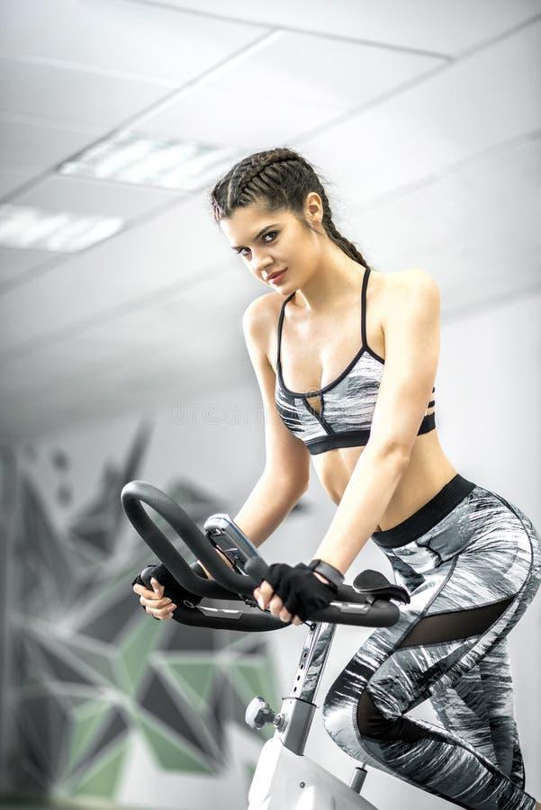 Девушка используя велосипед фитнеса стоковое фото rf