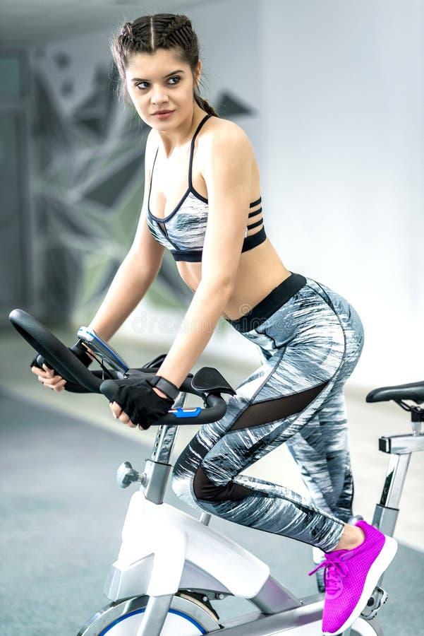 Девушка используя велосипед фитнеса стоковые изображения