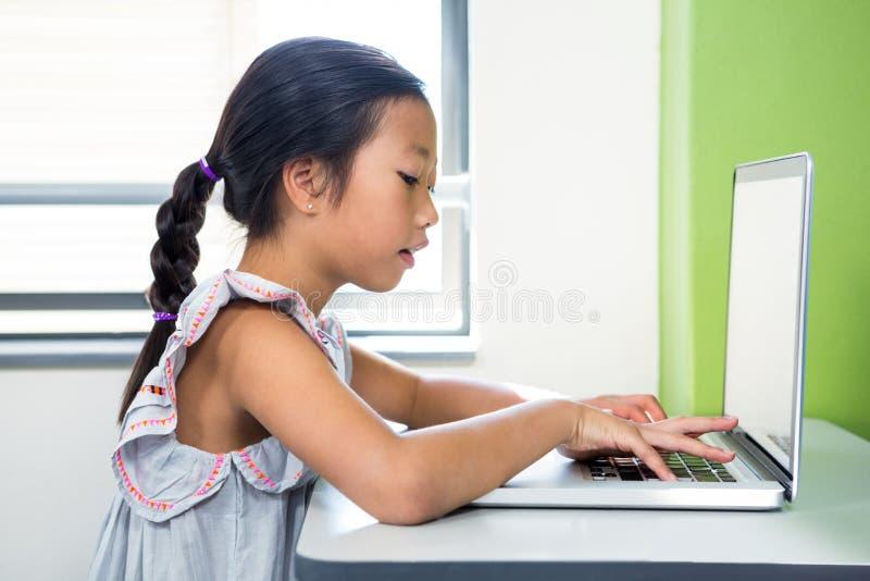 Девушка используя компьтер-книжку в классе стоковое фото