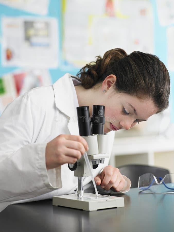 Девушка используя микроскоп в лаборатории стоковое фото