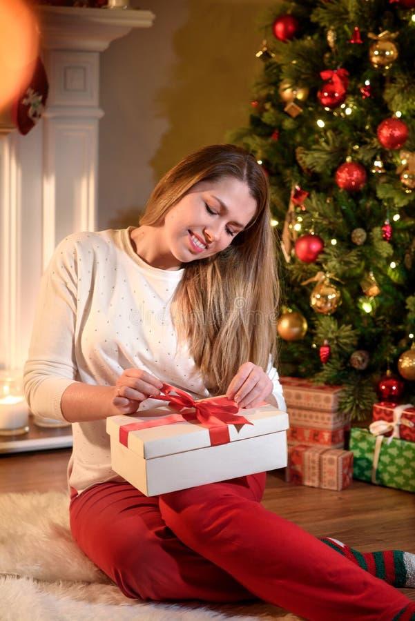 Девушка исправляя лента на усмехаться подарочной коробки Нового Года стоковое фото rf