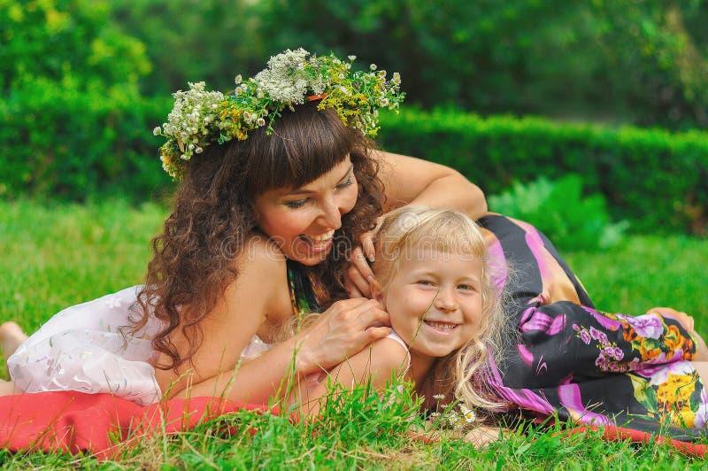 Девушка и ее мама между зеленой травой стоковое изображение rf