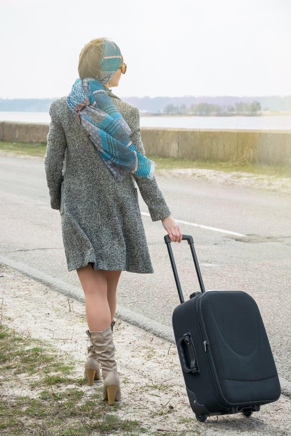 Девушка идет вдоль дороги морем с чемоданом стоковая фотография