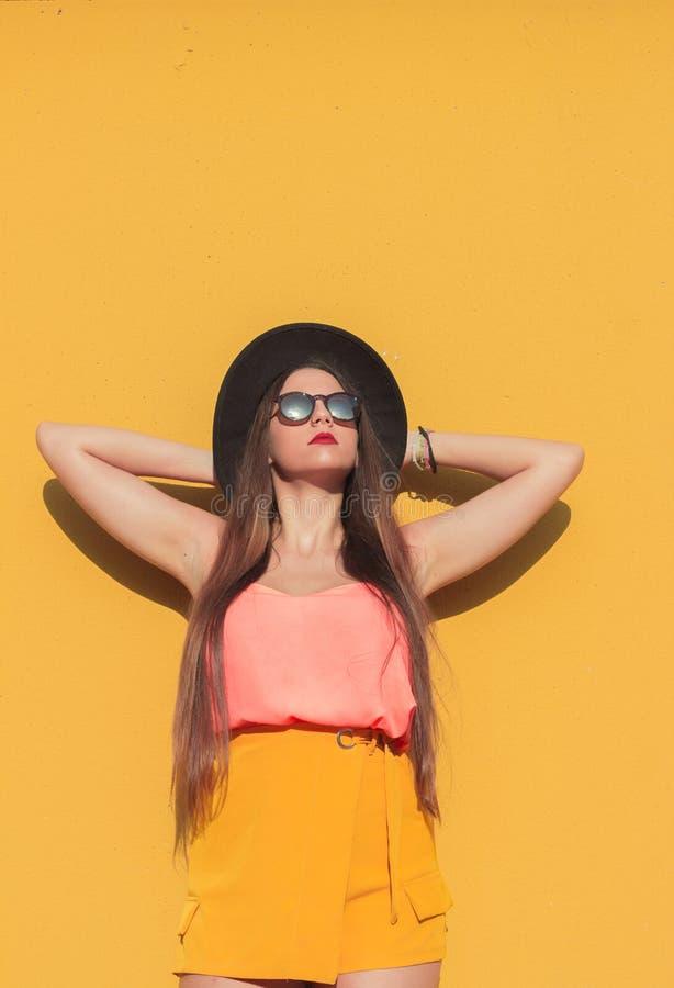 Девушка и желтая стена стоковые изображения rf