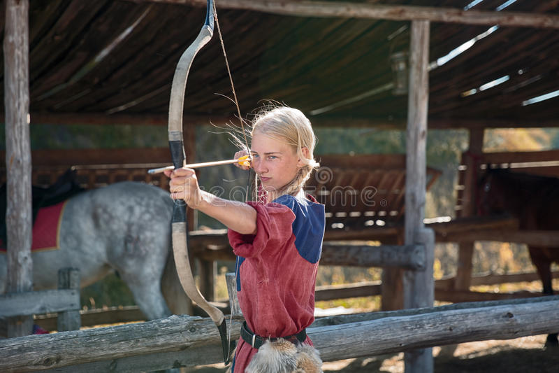 Девушка или милая стрельба женщины, лучника или охотника с луком и стрелы на солнечный день на стабилизированной цели на связках  стоковые фото