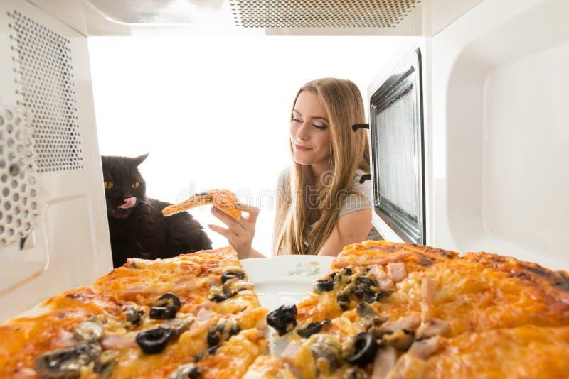 Девушка и кот смотря в микроволне стоковые фото