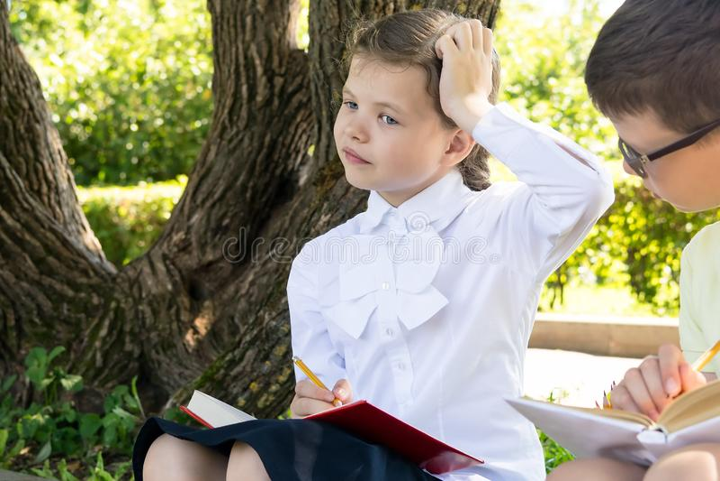 Девушка и мальчик думают о разрешать проблему в уроке будучи придержанными в природе стоковая фотография