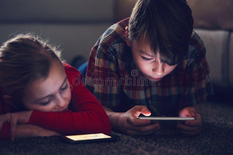 Девушка и мальчик с их умными телефонами стоковые фотографии rf