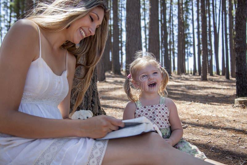Девушка и мать читая книгу стоковые изображения rf