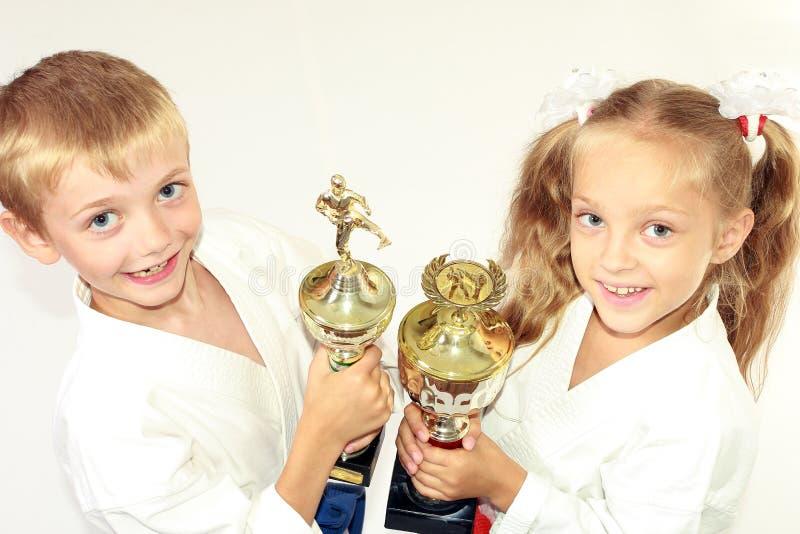 Девушка и мальчик в кимоно с чемпионатом выигрывая в руке на белой предпосылке стоковая фотография