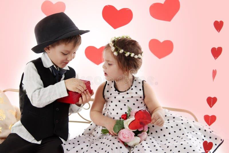 Девушка и мальчик сидя совместно как дама и джентльмен давая pre стоковые фотографии rf