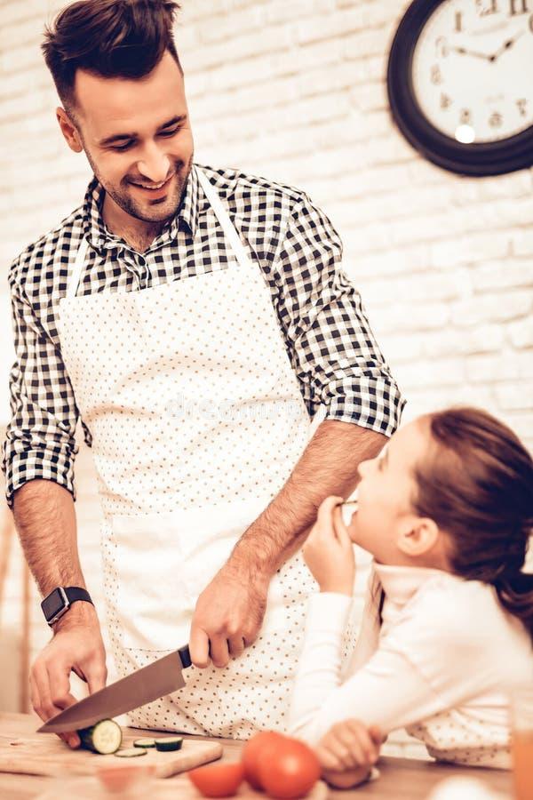 Девушка и отец с ножом отрезали овощи на борту стоковая фотография