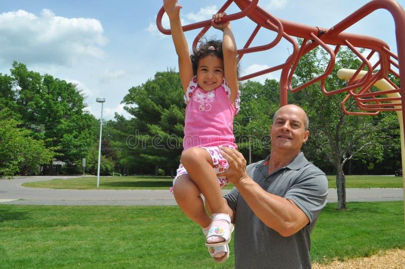 Девушка и папа в спортивной площадке стоковое фото rf