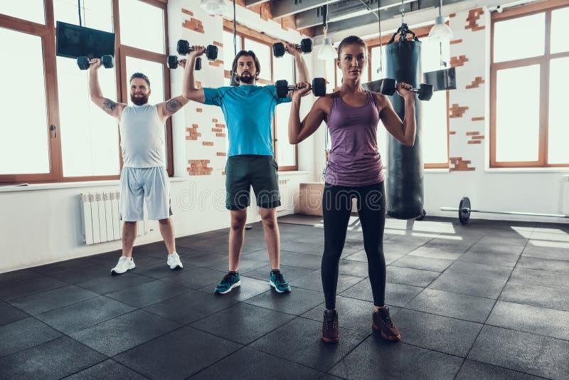 Девушка и 2 парня поднимая гантели в спортзале стоковое фото