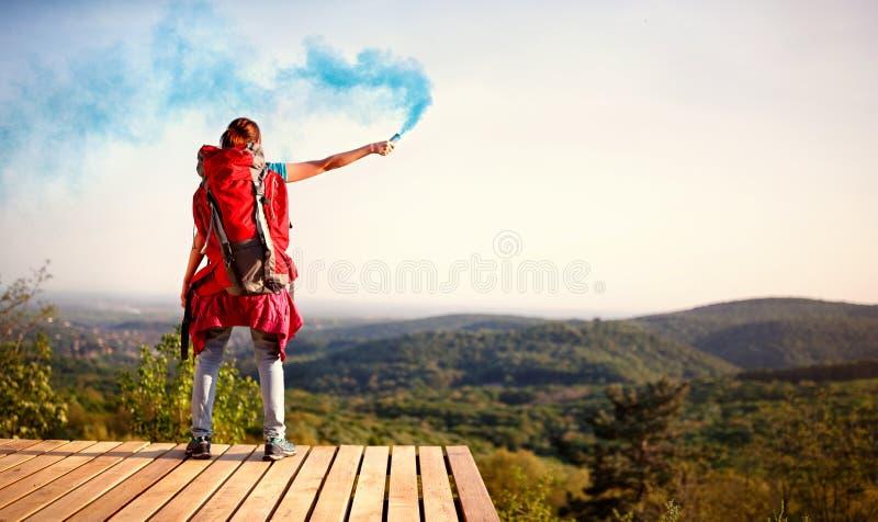 Девушка и показывая факел сигналов дыма стоковое фото