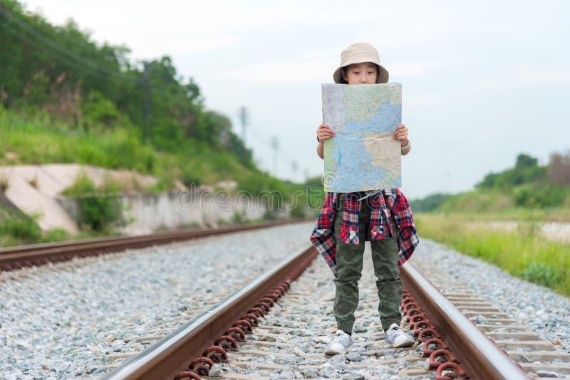 Девушка и путешественник студента азиатские с картой удерживания приключения рюкзака для обнаружения направлений около trai стоковые изображения rf