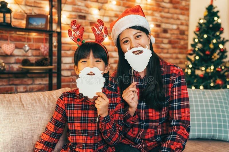 Девушка и ребенок Санта с оленями на голове имея потеху стоковое фото