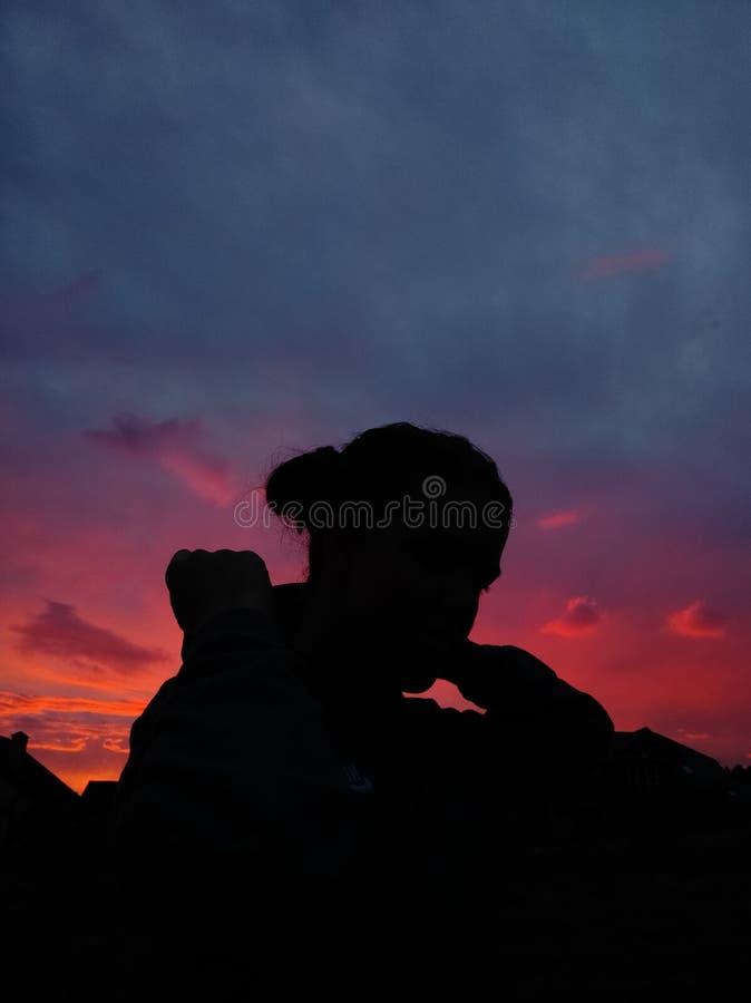Девушка и розовый заход солнца стоковое фото