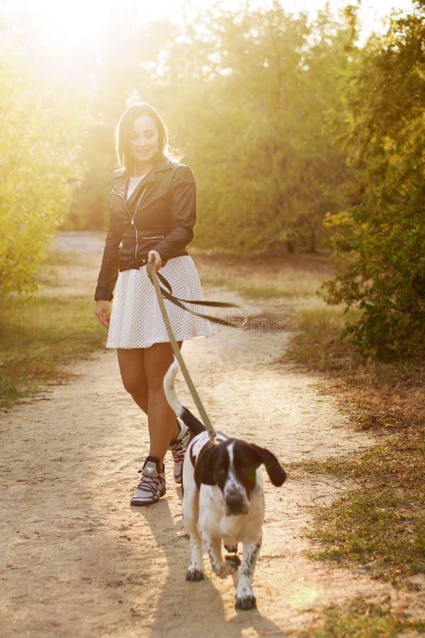 Девушка и собака в парке осени стоковая фотография