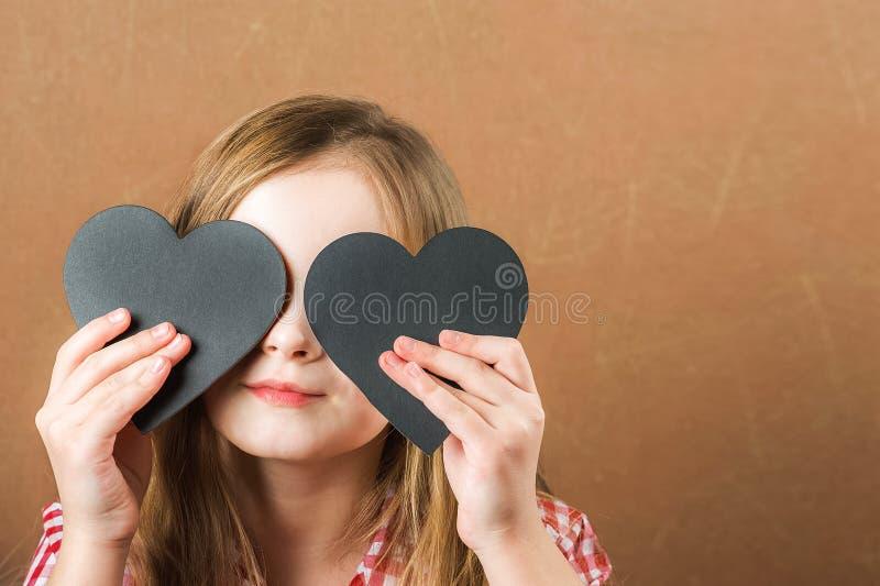 Девушка и черное сердце шифера Девушка строит физиогномику, гримасы и сердце для надписи Концепция дня Валентайн, конец стоковые фото