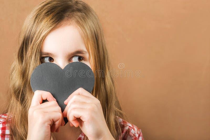 Девушка и черное сердце шифера Девушка строит физиогномику, гримасы и сердце для надписи Концепция дня Валентайн, конец стоковое фото rf