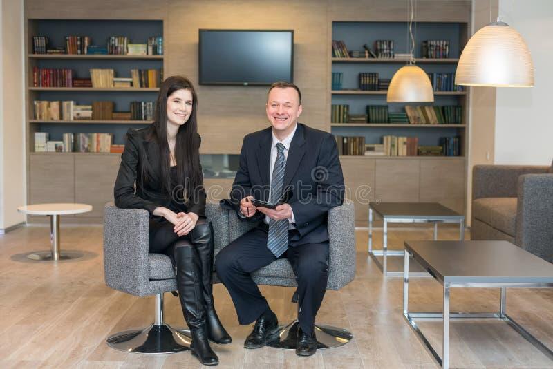 Девушка и человек в деловых костюмах сидя с блокнотом стоковые изображения rf