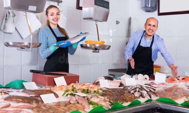 Девушка и человек представляя около дисплея стоковые изображения rf