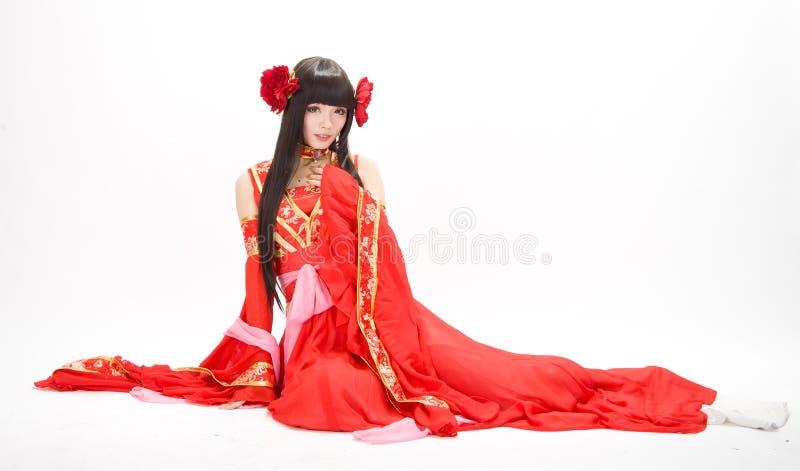 Девушка китайского стиля Азии в красном традиционном танцоре платья сидит стоковое изображение
