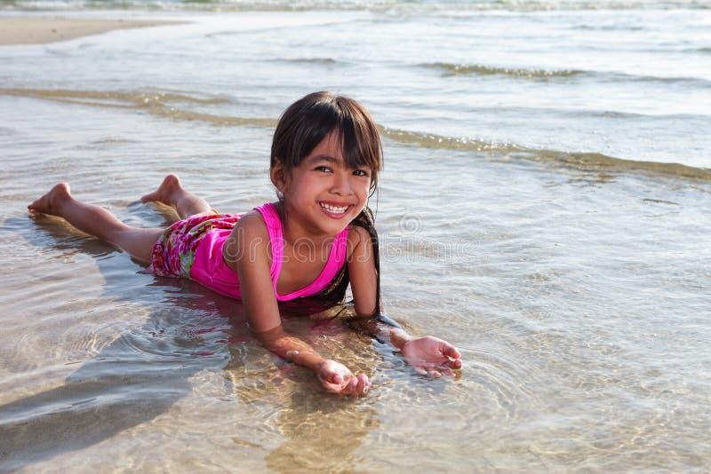 Девушка кладя в воду на пляж стоковое изображение