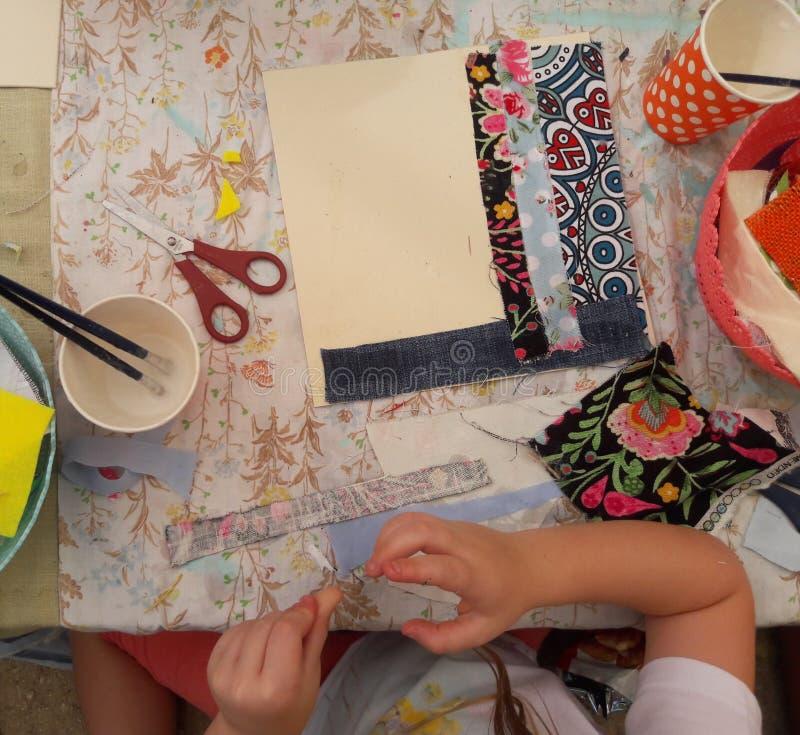 Девушка клеит и режет ткань в изображение стоковое фото rf