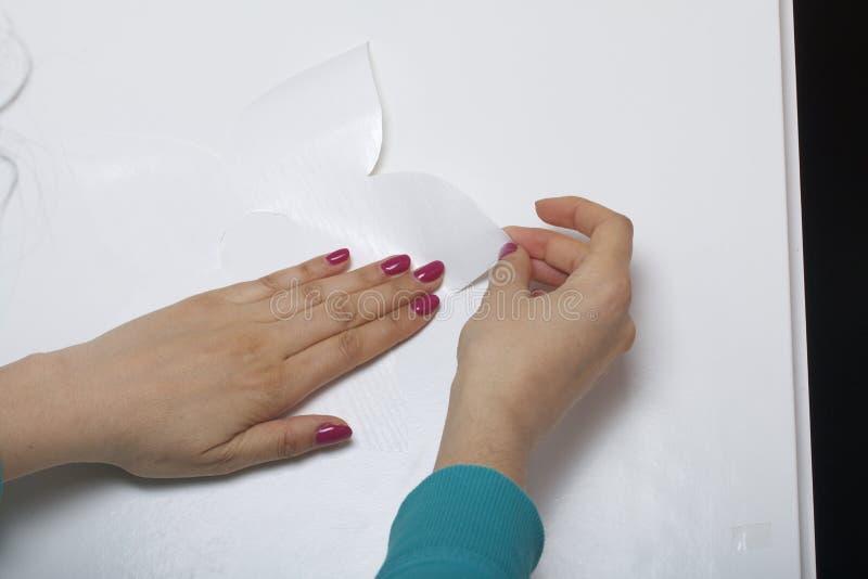 Девушка клеит элементы отрезка вне от бумаги само-прилипателя, для того чтобы замаскировать дефекты белой двери стоковое фото