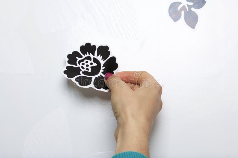 Девушка клеит элементы отрезка вне от бумаги само-прилипателя, для того чтобы замаскировать дефекты белой двери стоковые изображения