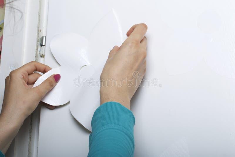 Девушка клеит элементы отрезка вне от бумаги само-прилипателя, для того чтобы замаскировать дефекты белой двери стоковые фото