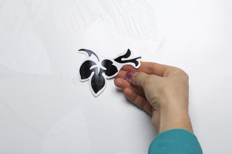 Девушка клеит элементы отрезка вне от бумаги само-прилипателя, для того чтобы замаскировать дефекты белой двери стоковое изображение rf