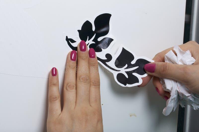 Девушка клеит элементы отрезка вне от бумаги само-прилипателя, для того чтобы замаскировать дефекты белой двери стоковая фотография rf