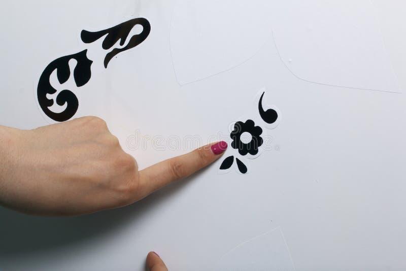 Девушка клеит элементы отрезка вне от бумаги само-прилипателя, для того чтобы замаскировать дефекты белой двери стоковые изображения rf