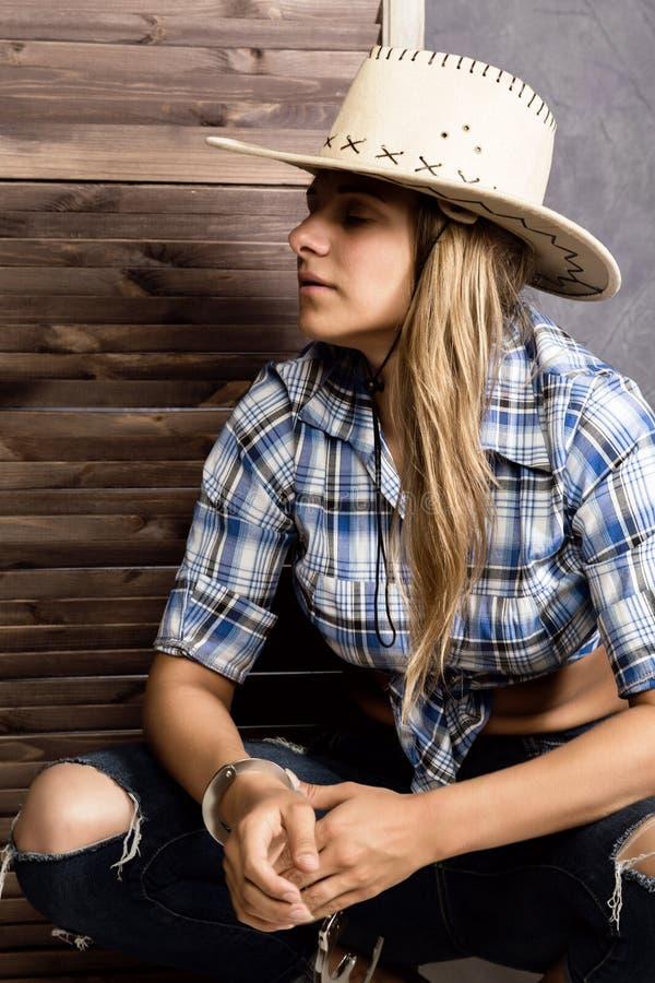 Девушка ковбоя или милая женщина в стильной шляпе и голубой рубашке шотландки держа оружие и старый чемодан стоковое фото