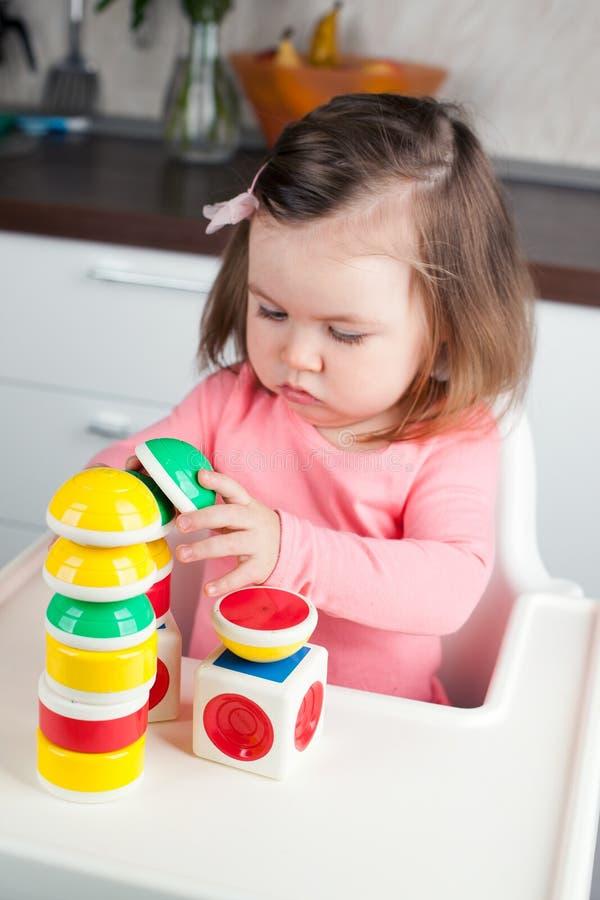 Девушка конструкции 2 года старого при длинные волосы играя с дизайнером дома, строящ башни, сконцентрировала ход стоковая фотография rf