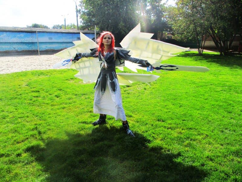 Девушка-косистка с огромными белыми крыльями, с мечами в броне стоковое фото