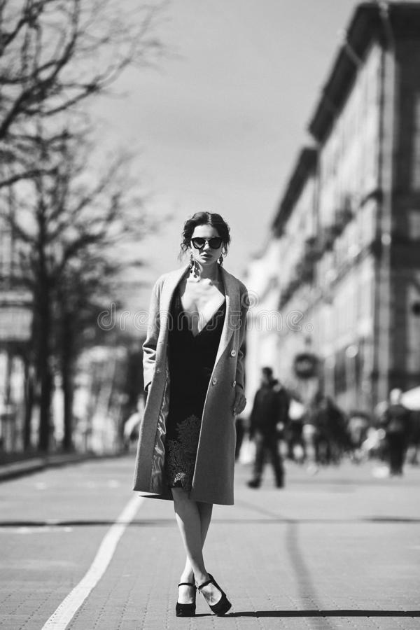 Девушка красивого и сексуального брюнета бесцветного фото - модельная в черном стильном платье, в ультрамодном пальто и внутри мо стоковые изображения rf