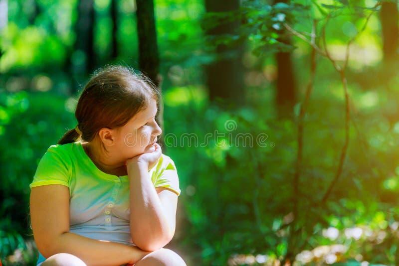 Девушка красивого маленького ребенка портрета милая смотря до одна сторона в парке сада стоковое изображение rf