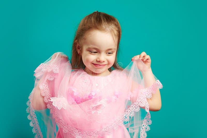 Девушка красивого ребенка держа кромку шнурка ее розового платья на голубом изолированный стоковое фото rf