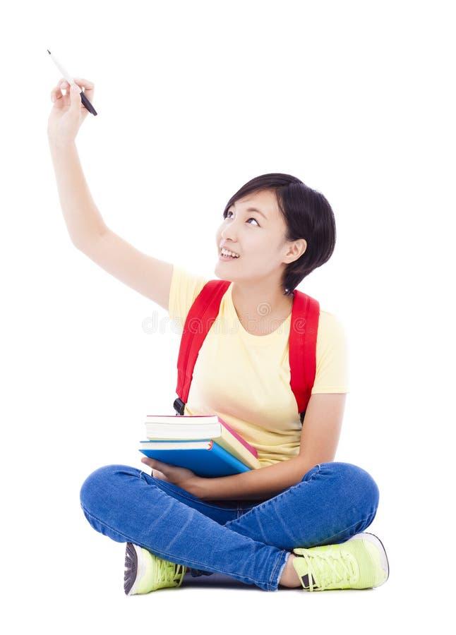 Девушка красивого студента азиатская сидя на поле и рисовать стоковые изображения