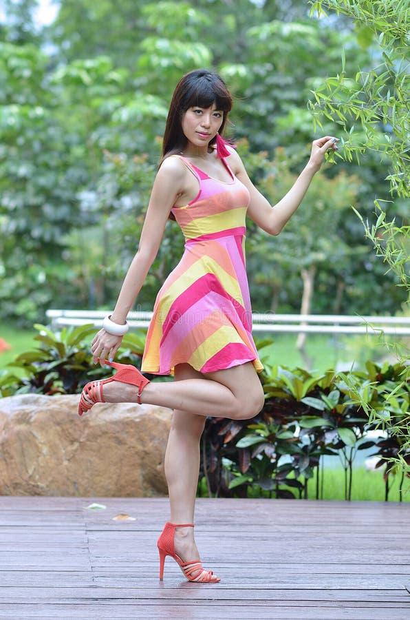 Девушка красивых и секса азиатская показывает ее молодость в парке стоковые фото