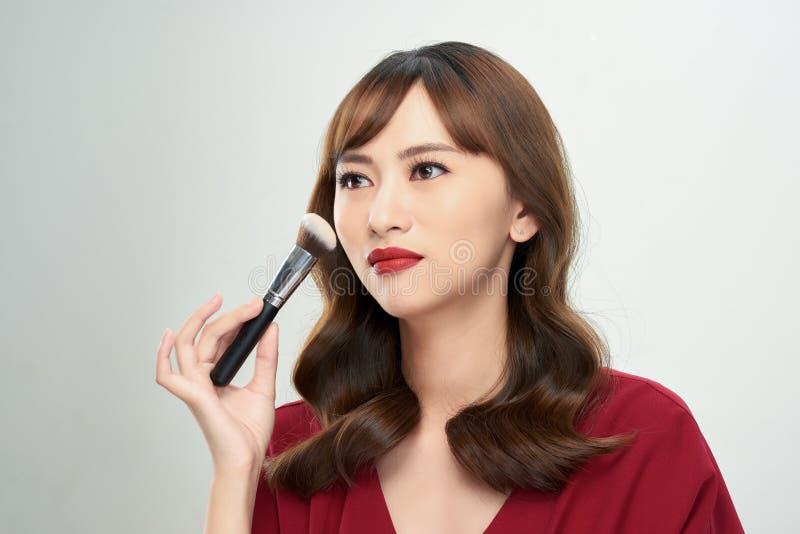 Девушка красоты азиатская загорает кожу с щетками макияжа Она усмехаясь и смотря для того чтобы напудрить щетку, естественный мак стоковые фото