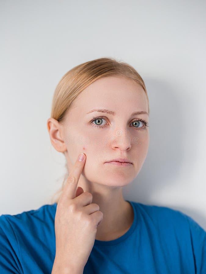 Девушка красоты которая проверяет ее кожу, заботу кожи, обработку угорь стоковая фотография rf
