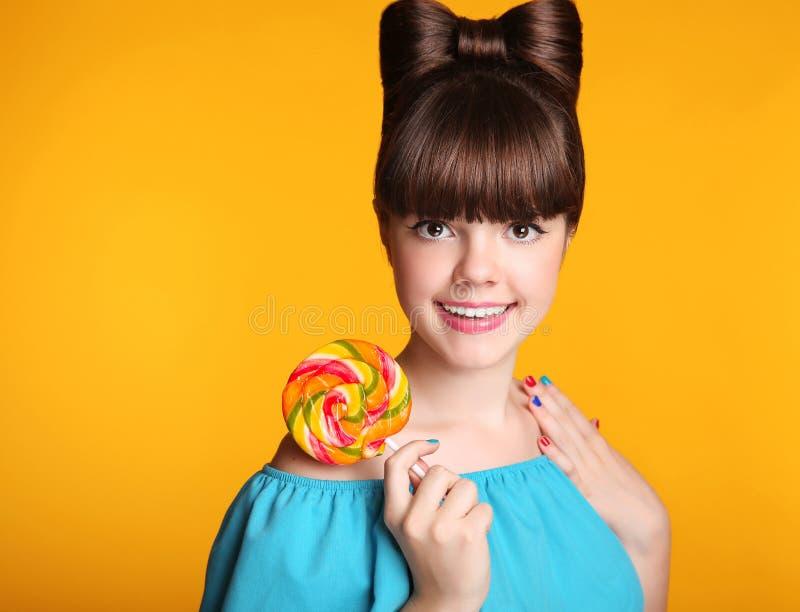 Девушка красоты счастливая усмехаясь предназначенная для подростков есть красочный леденец на палочке Lollyp стоковые изображения rf
