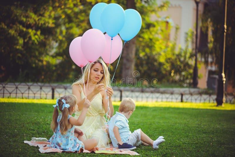 Девушка красоты с красочными воздушными шарами смеясь с 2 детьми Красивая счастливая молодая женщина на прогулке в парке Одно, ко стоковое изображение rf