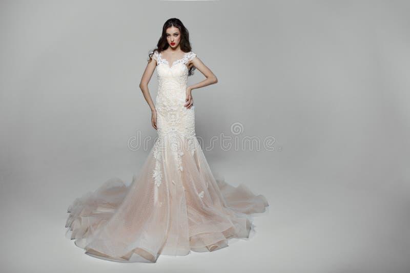 Девушка красоты с курчавыми длинными волосами в белом платье свадьбы с вышивкой, изолированной на белой предпосылке стоковые изображения rf