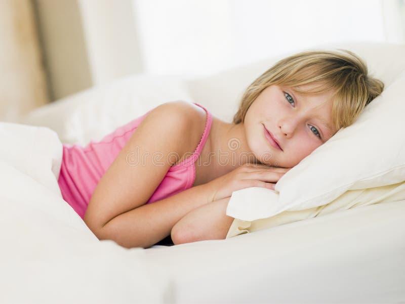 девушка кровати ее лежа детеныши стоковое фото